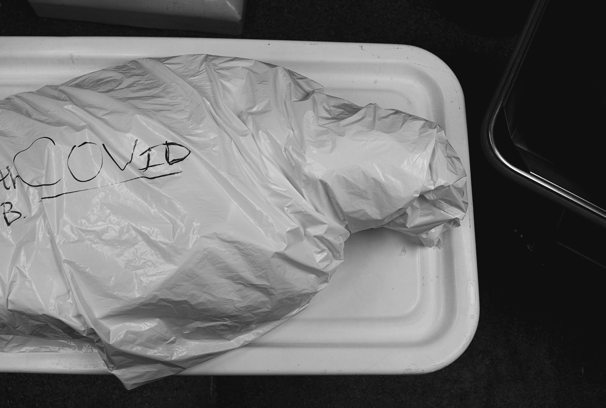 "A body wrapped in plastic with the word ""COVID"" written on it"