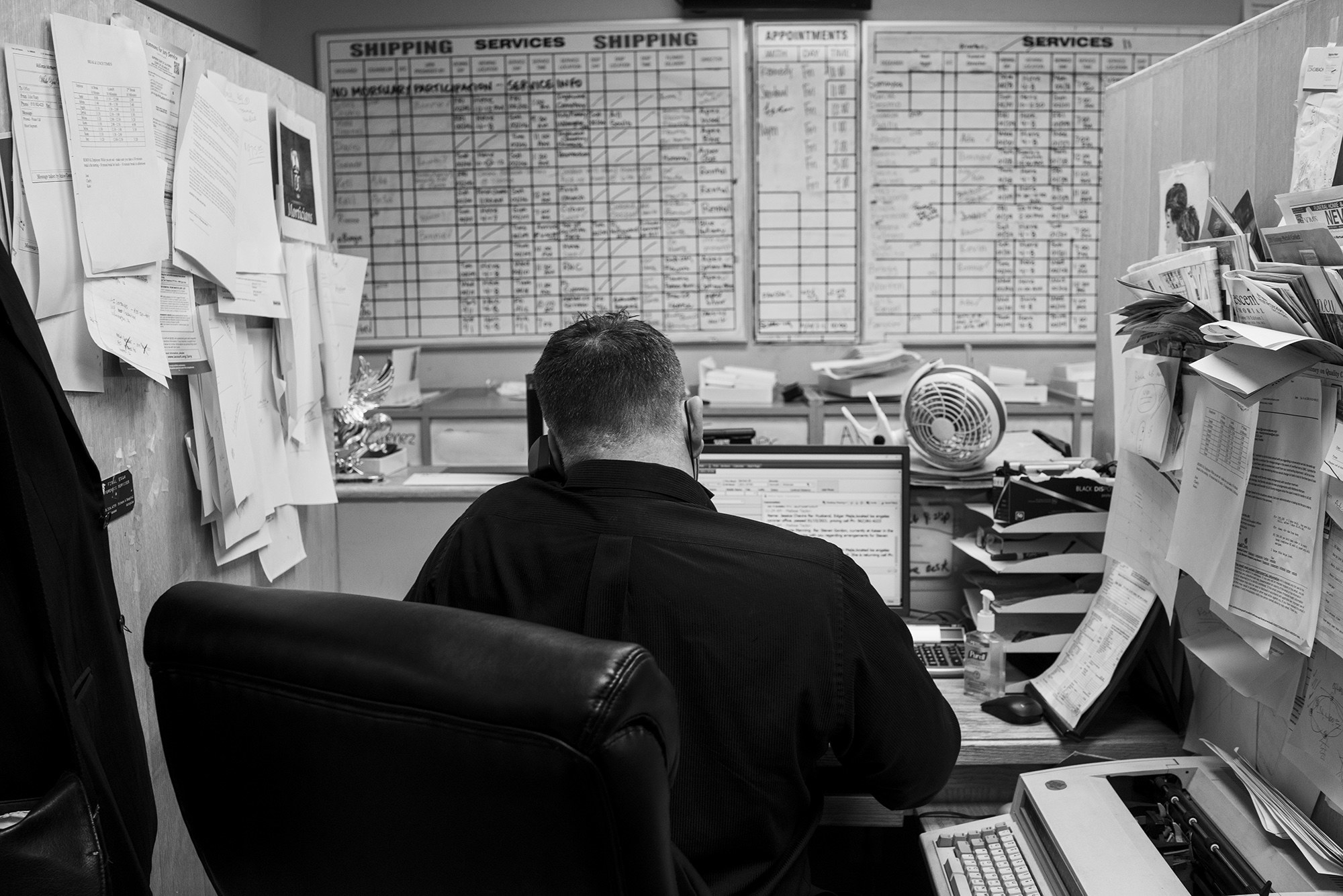 A man seen from behind at a desk covered with papers and a full calendar