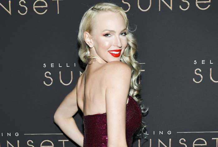 Christine poses on a red carpet in a shimmering strapless red dress