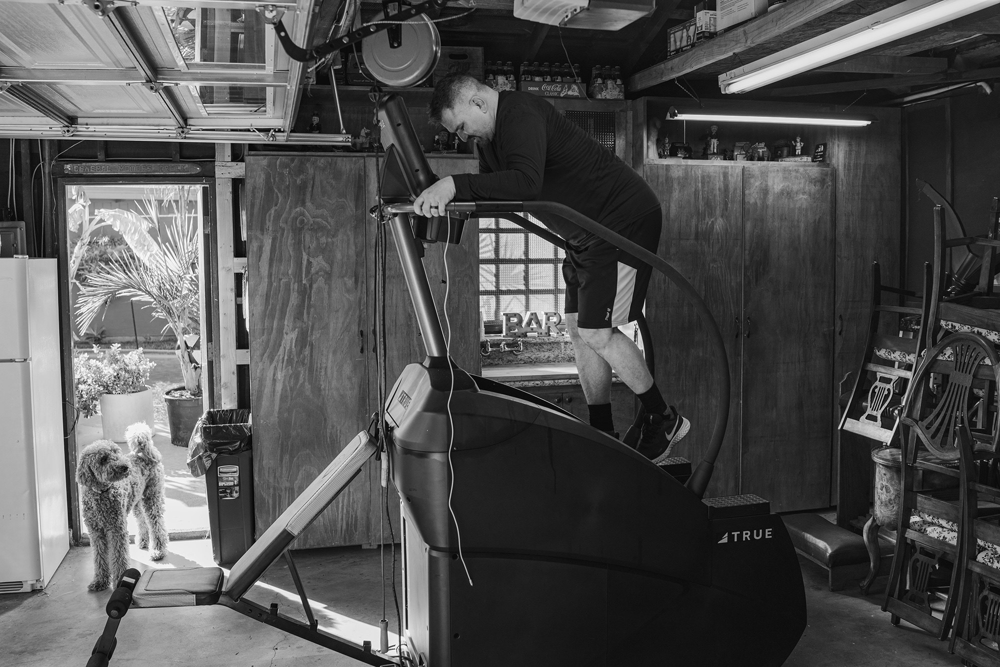A man on a stairmaster in a garage while a dog watches, a pile of chairs is behind him