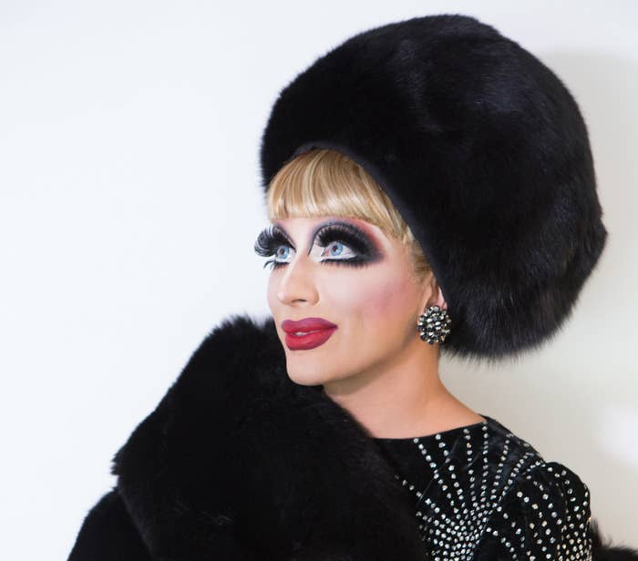 Bianca looking toward the upper left side while wearing a black fur stole with matching box hat