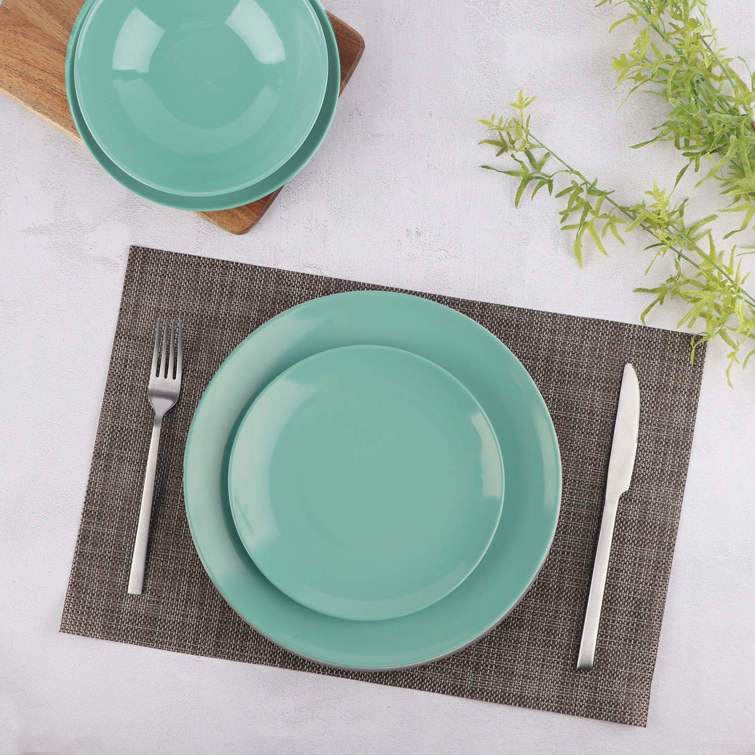 A teal dinner plate with a quarter plate on top of it on a placemat