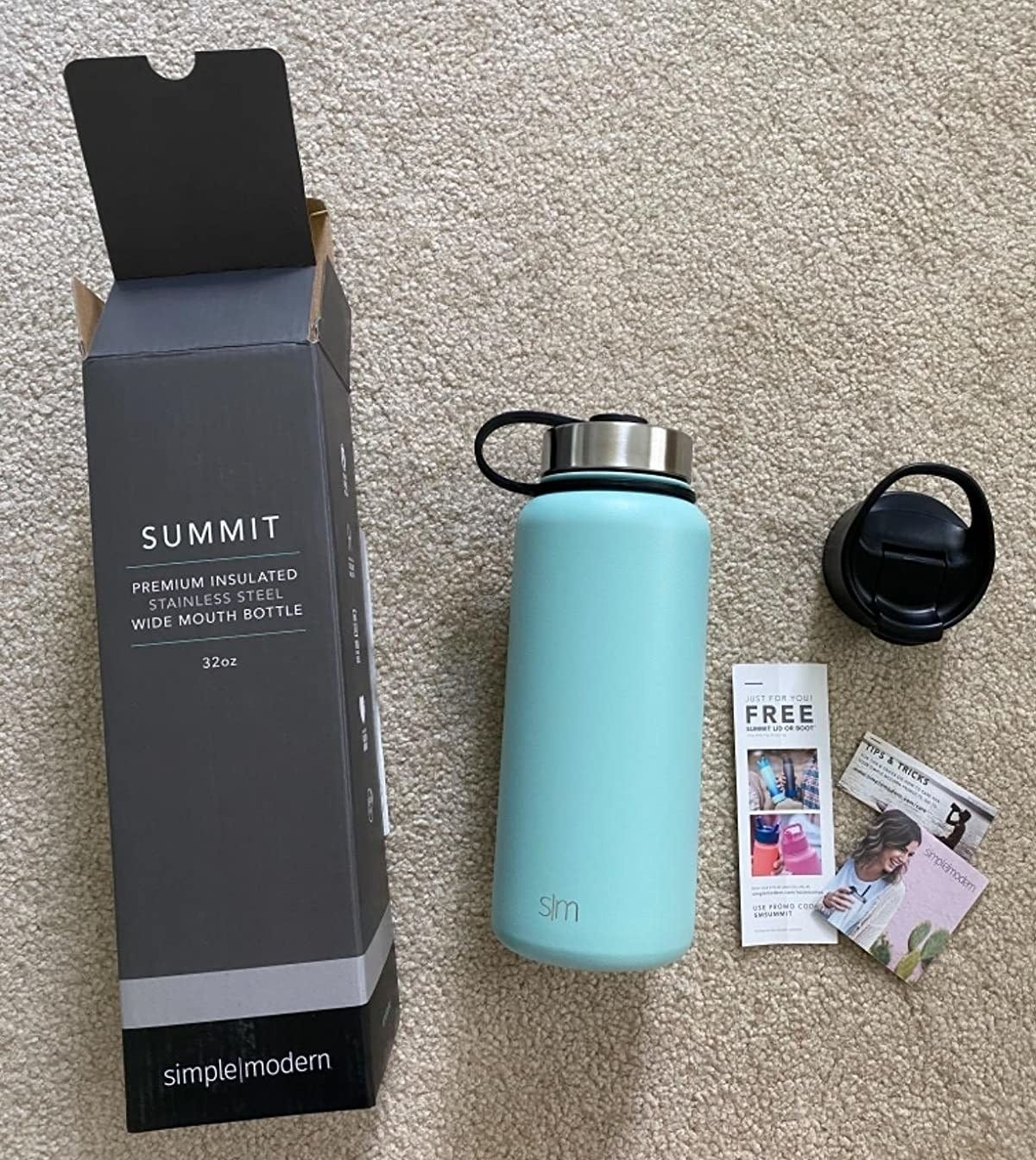 reviewer photo showing the water bottle in blue and the packaging it came in