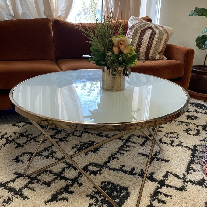 """Reviewer's picture of the table, which has a glass-covered, rounded top, over four sets of crossed """"V"""" legs"""