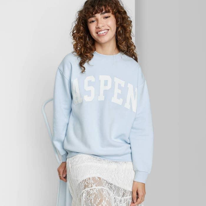 """model in light blue pullover that reads """"Aspen"""""""