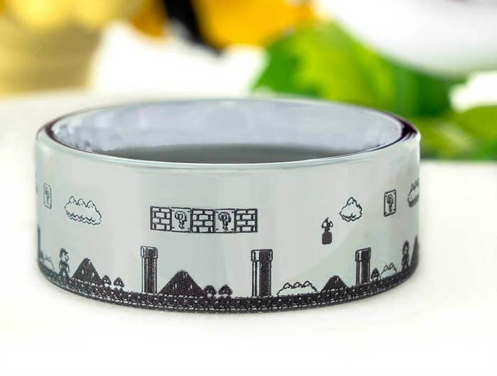 A silver band ring engraved to look like a side-scrolling level of Super MArio Bros