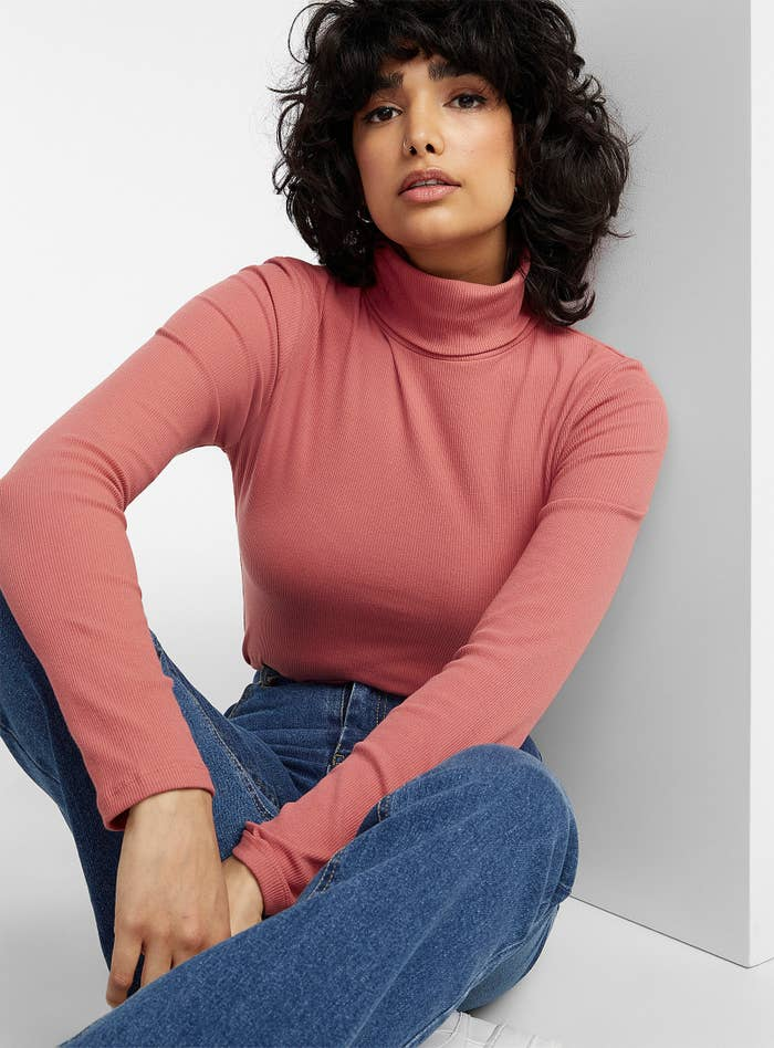 A person wearing a turtleneck sweater and jeans
