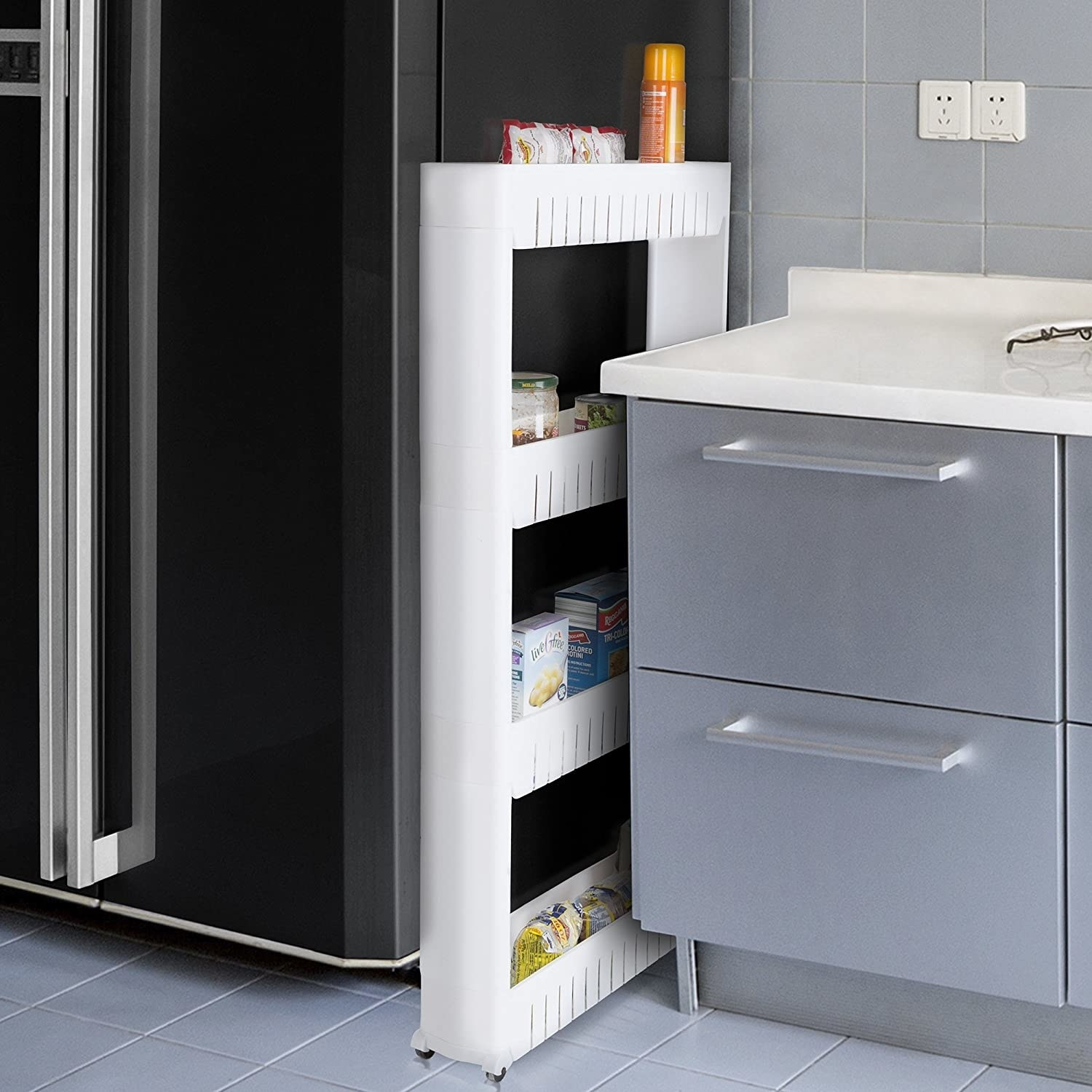 A slim white four-shelved organizer with wheels between a fridge and a counter