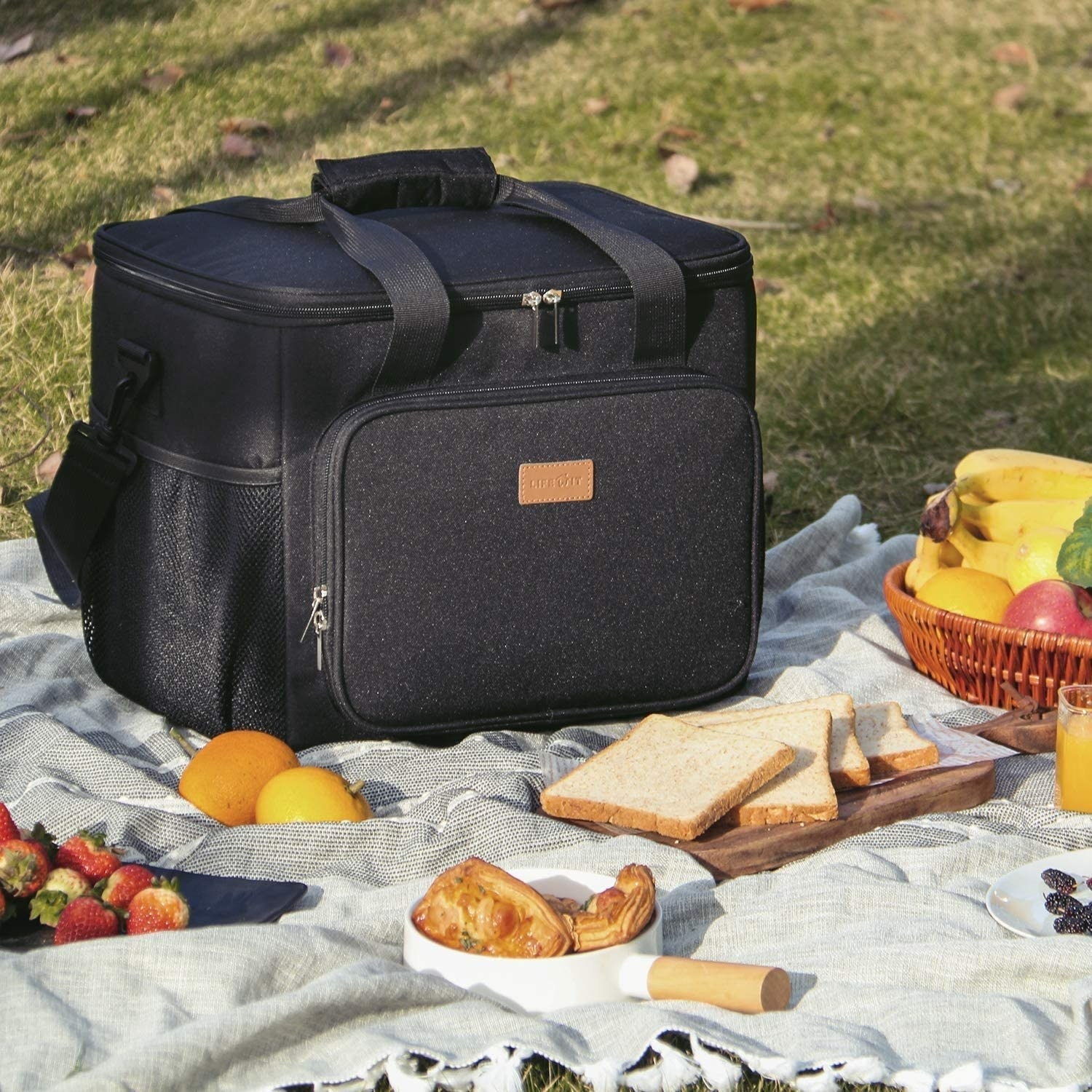 Canvas cooler with handles, crossbody straps, and several pockets on top of a picnic blanket with food around it