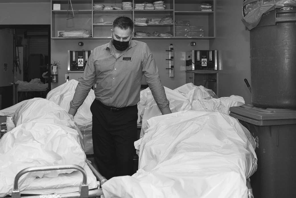 A man stands surrounded by body bags