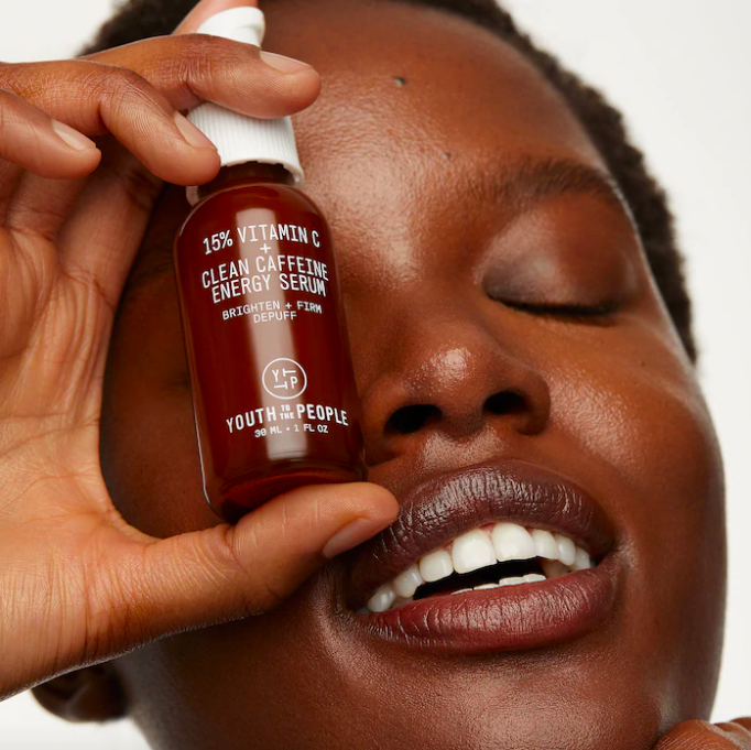 A smiling person holding up the serum to their face