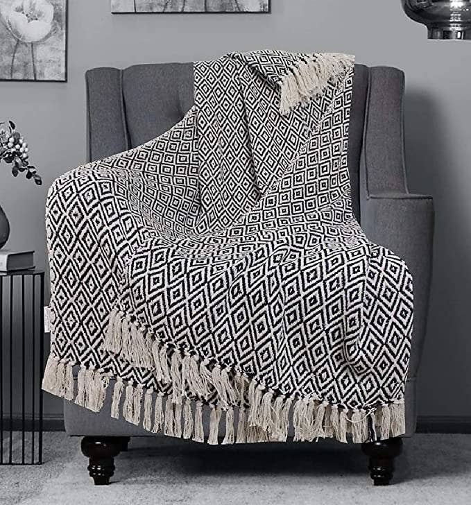 Monochrome geometric throw blanket with tassels at the ends.