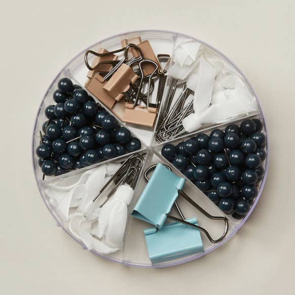 A transparent circular organizer filled with binder clips, push pins, and paper clips