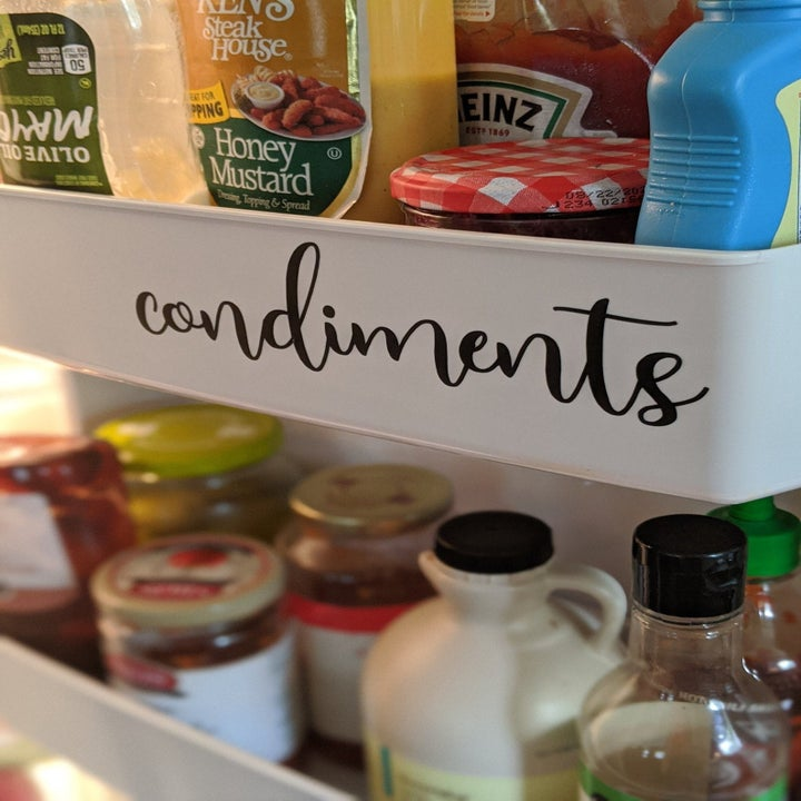 "Image of a fridge shelf with a black cursive sticker label that says ""condiments"""