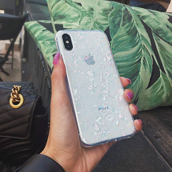 A person holding up an opalescent phone case