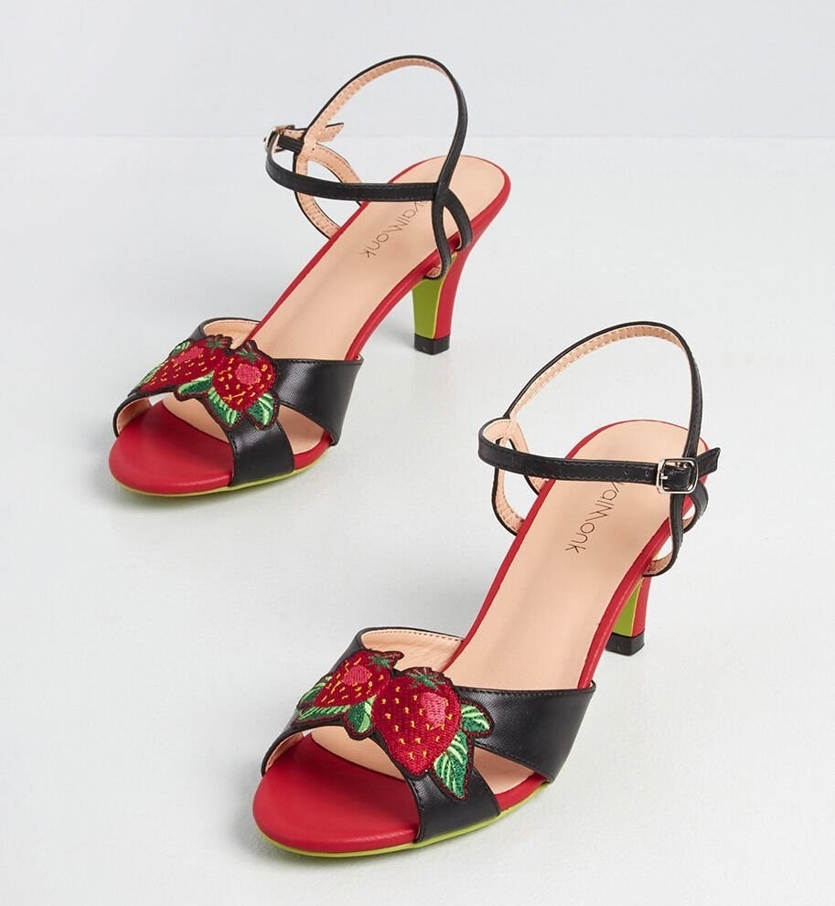 red and black kitten heels with ankle straps and strawberries across the toes