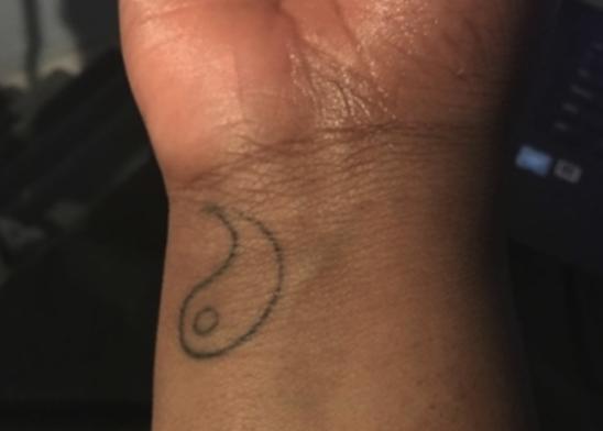Half of a yin-yang symbol on someone's wrist