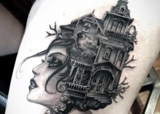 A tattoo of a woman's head with a haunted house as her hair