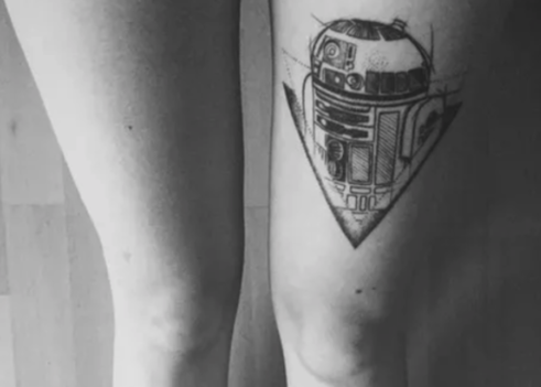 A detailed thigh tattoo of R2D2