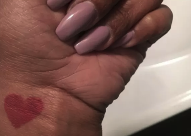 A tiny red heart on someone's wrist