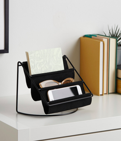 The hammock organizer on a desktop, holding a phone, a pair of glasses, and a notebook