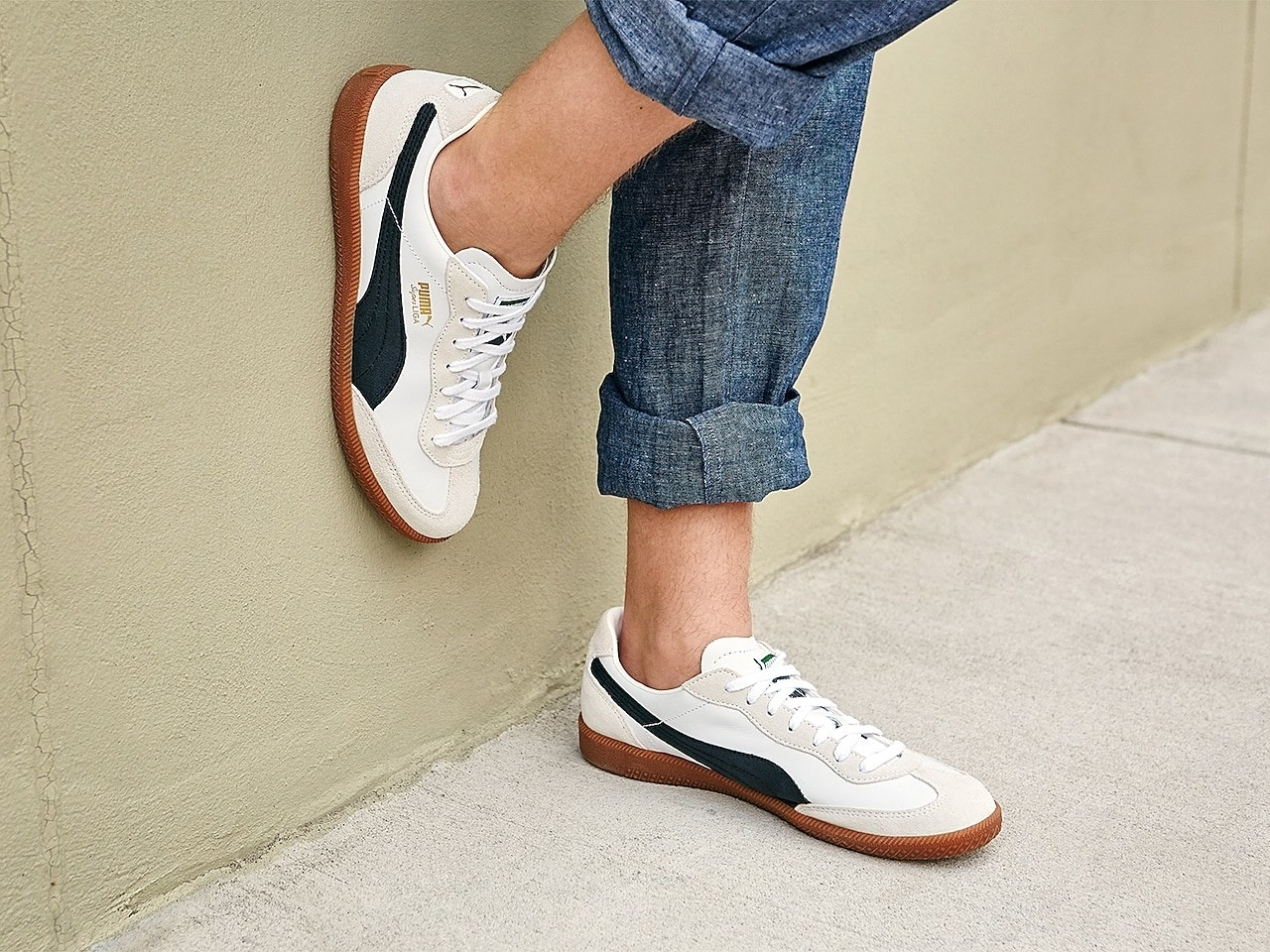 model wearing the beige and white sneakers with tan sole and blue wave on the sides