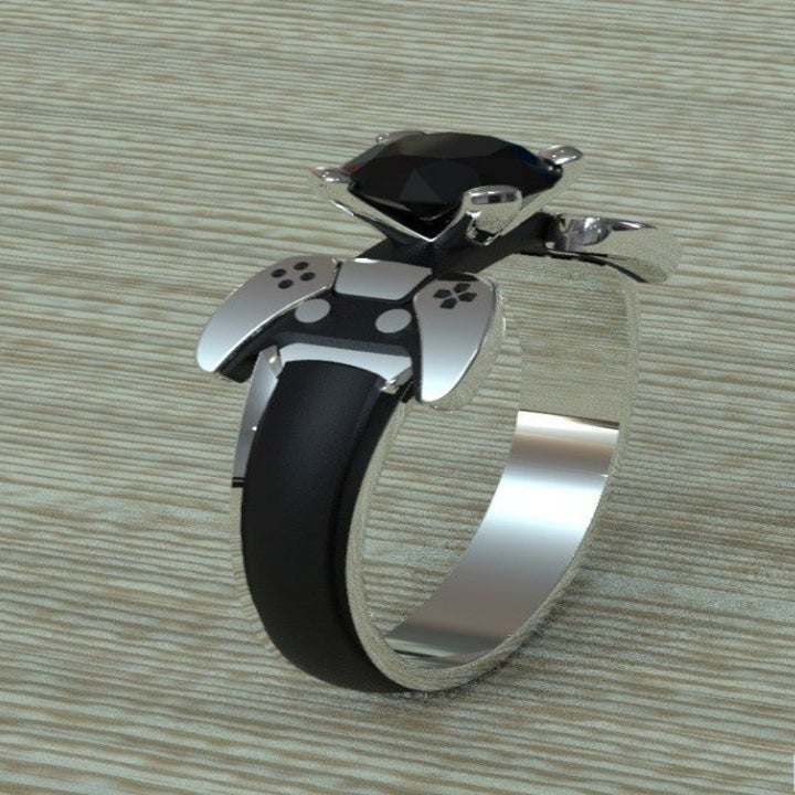 A black and silver ring with a black stone flanked by controller-shaped accents