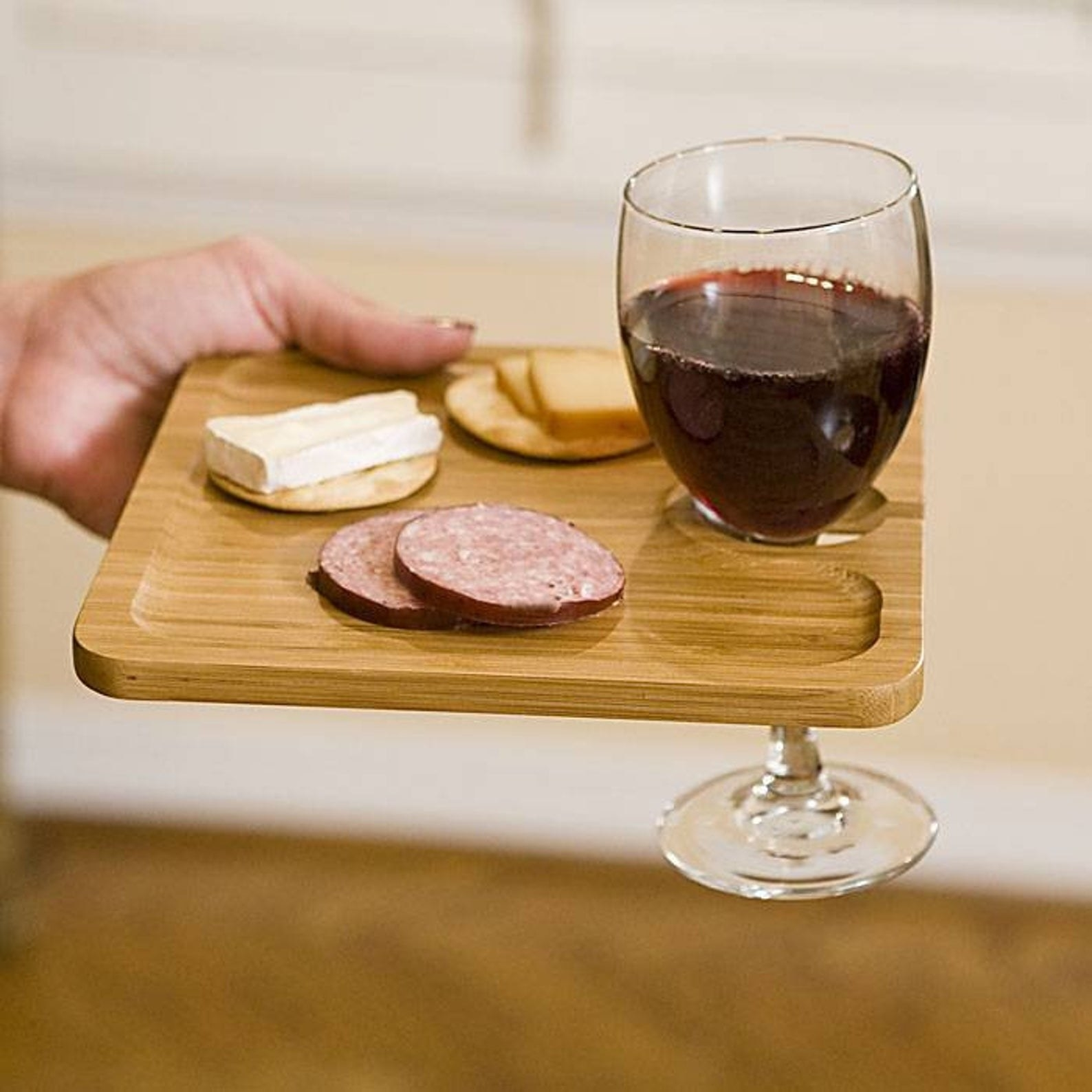 A model holding an individual light wood cheese plate with a small hole a wine glass can rest in