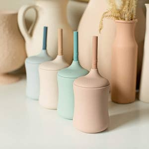 Four modern sippy cups with built-in straws