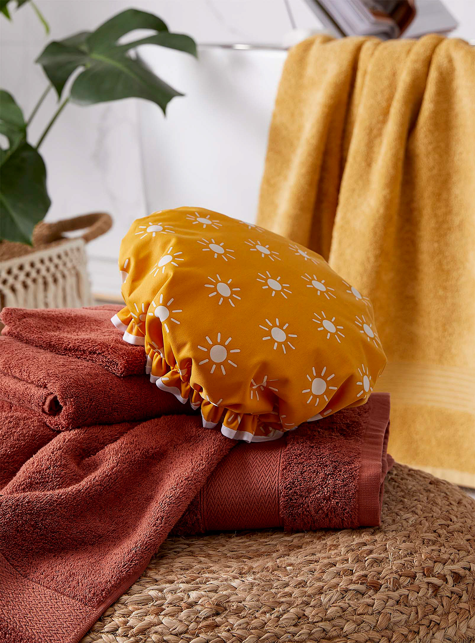 A shower cap with a sun pattern on it lying on a folded towel