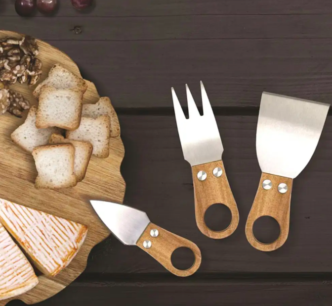 A flatlay of the three cheese knives next to a cheese platter