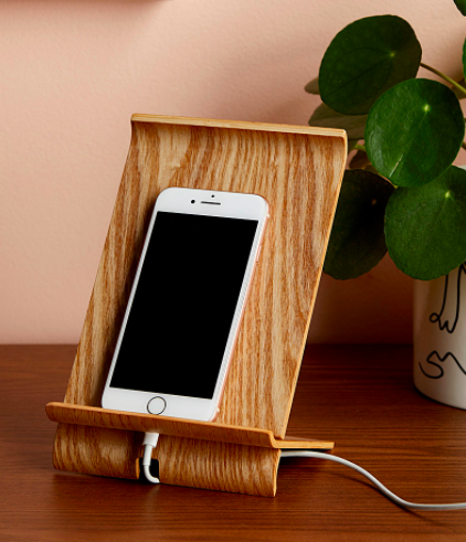 A phone perched on the wooden dock with the charging cable coiled underneath