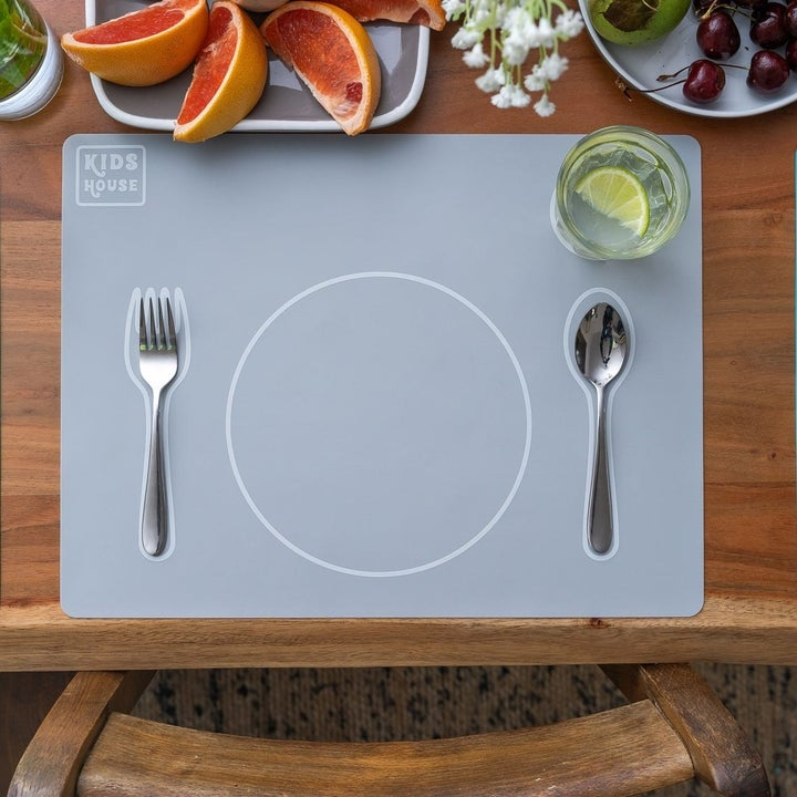 Gray placemat with outlines for a fork, spoon, and plate