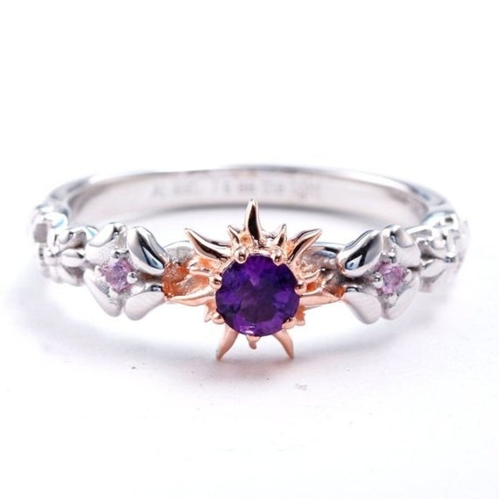 The ring with a center amethyst, sunburst setting, and a band with a braided floral motif