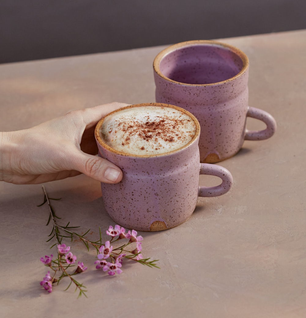 a hand holding the pink speckled stoneware mug