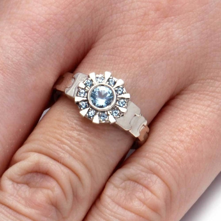 """A hand wearing the ring featuring the reactor from """"Iron Man"""" with an aquamarine gem in the center"""