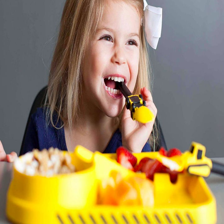 Child smiling while eating from a spoon with a truck on it