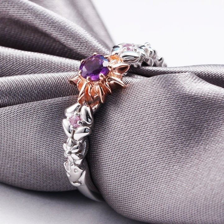 The ring on a gray napkin with a center amethyst, sunburst setting, and a band with a braided floral motif