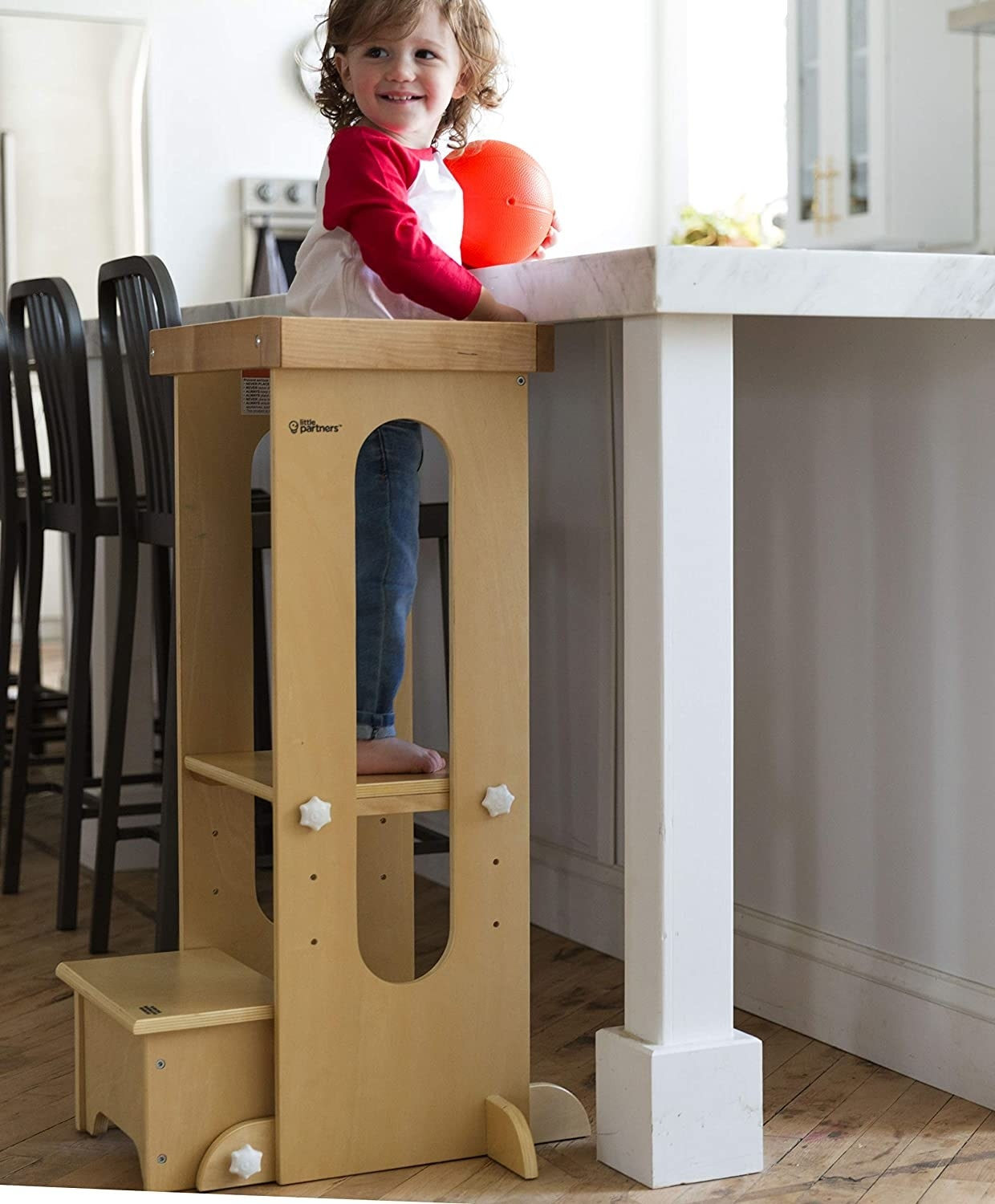 Child standing up by counter. They are able to reach thanks to the adjustable extra step and stay safe with a barrier bar in the back.