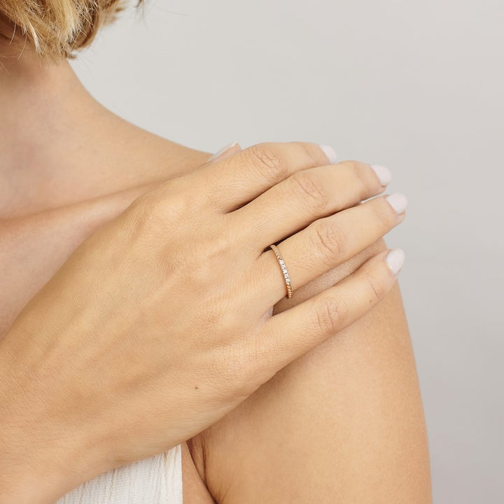 A model wearing a slim gold band with a chevron pattern and five diamonds