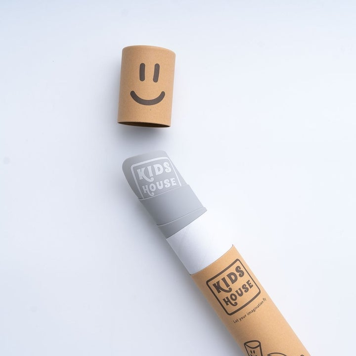 The mat inside a cardboard tube with a smily face top