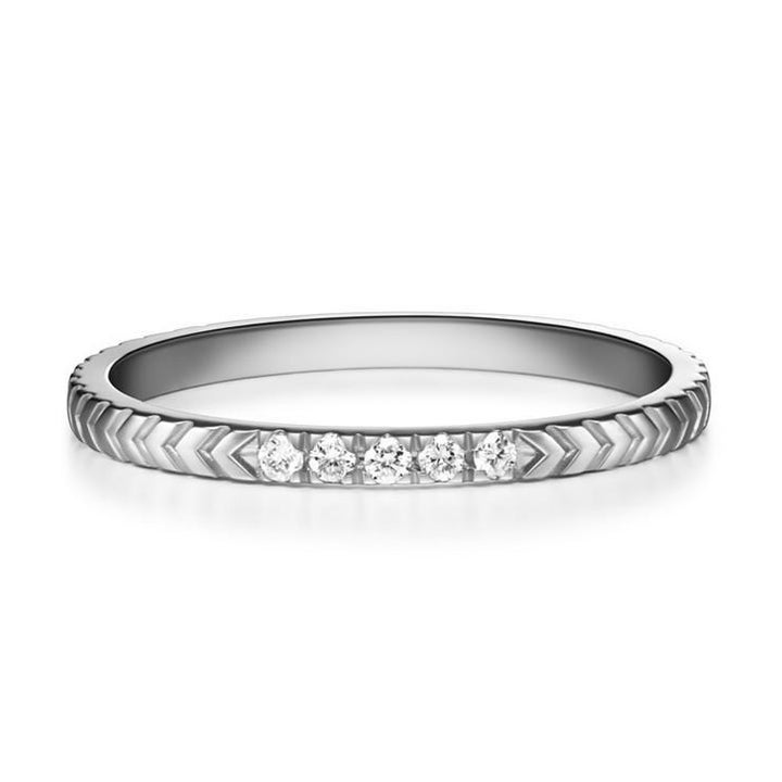 A closeup of the ring in silver with a geometric pattern and five diamonds