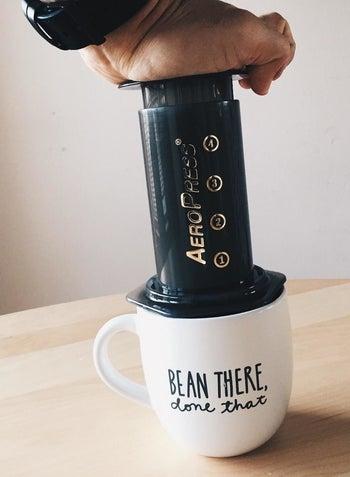 a reviewer using the Aeropress over a mug
