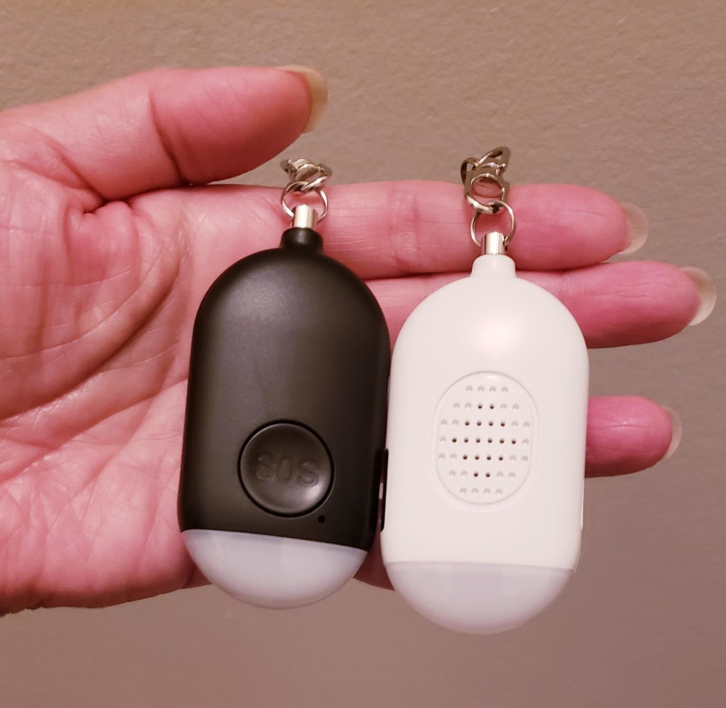 Reviewer holding SOS keychain alarm