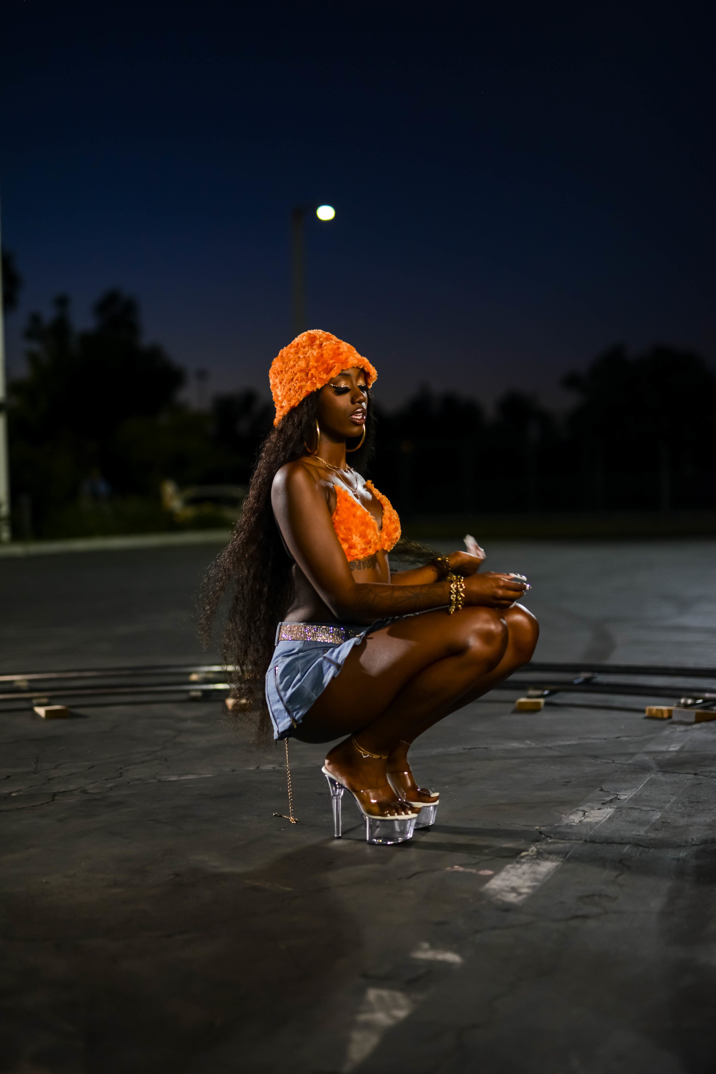 Flo Milli in an orange outfit on a music video set