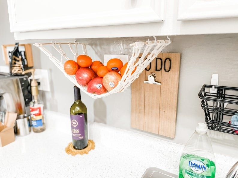 white macrame fruit hammock with oranges and apples above a small kitchen counter