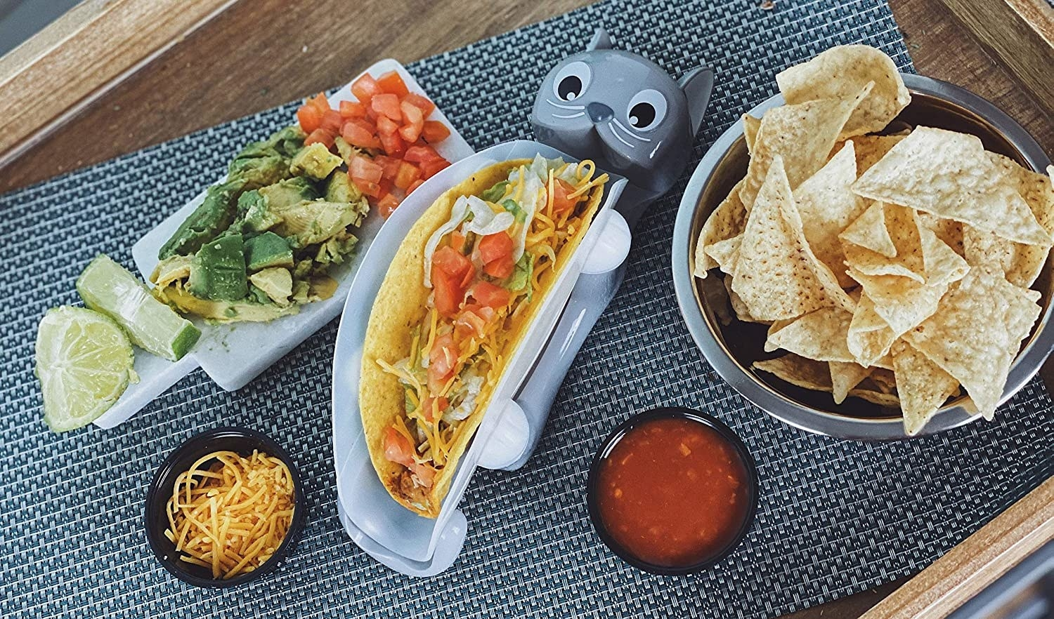 Clear taco holder with a base shaped like a cat laying on it's back. The legs hold up the plastic container.