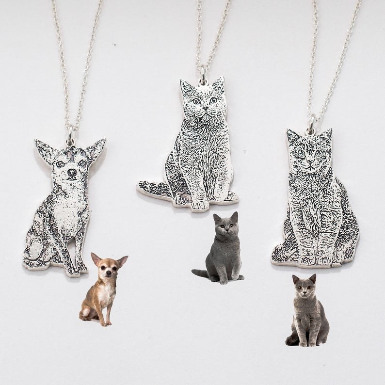 silver engraved pet-shaped pendants next to pictures of the pets they're based on