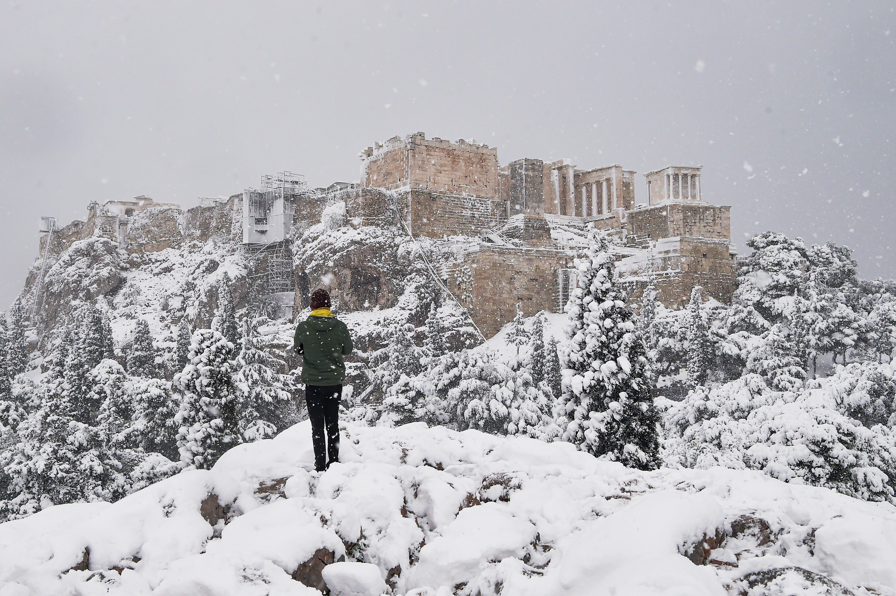 A man staring at a snowy Greek ruin