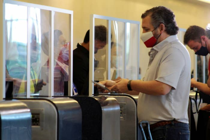 Ted Cruz, wearing a face mask with the Texas flag, checks in at an airport in front of a plexiglass shield